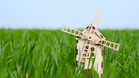 Agriculture et agriculture Un petit moulin décoratif fait de supports en bois parmi l'herbe verte d'un champ de blé banque de vidéos