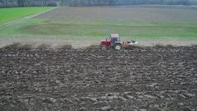 Agriculture and farming - Aerial view of tractor ploughing a field in early spring stock video