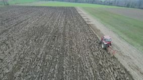 Agriculture and farming - Tractor plough a field in early spring aerial footage stock video footage