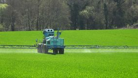 Agriculture fertilizer working on farming field, agriculture machinery working on cultivated field and spraying
