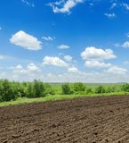 Agriculture field and blue sky with clouds. Black agriculture field and blue sky with clouds Stock Photo