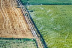 Agriculture fields with irrigation machines working. Long shot of agriculture fields with irrigation machines working Royalty Free Stock Photos