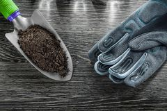 Agriculture hand spade soil safety gloves on wooden board Royalty Free Stock Photos