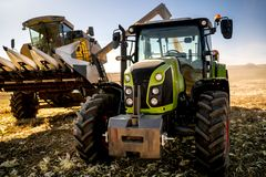 Agriculture industry machinery. Combine harvester and tractor with trailer unloading harvest. Farmer details stock photo