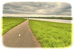 Road, Dam and Canal in Holland. Agriculture on Land Reclaimed from the See in Netherlands. Asphalt road along protective dam and canal in Holland Royalty Free Stock Photography