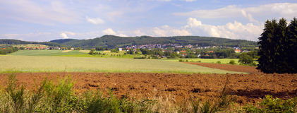 Agriculture landscape. With plowed field,  in the distance country Dueppenweiler, Saarland / Germany. Stitched panorama Royalty Free Stock Photos