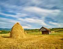 Agriculture Landscape. Time lapse landscape with haystack, small barn, yellow filed and dramatic blue sky Royalty Free Stock Photo