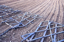 Agriculture machinery harrow rake on plowed field Stock Images