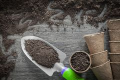 Agriculture peat pots soil spade on wooden board Royalty Free Stock Photo