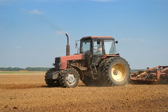 Agriculture ploughing tractor outdoors. Agriculture tractor in yellow field outdoors in summer with plough Royalty Free Stock Photo