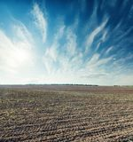 Agriculture plowed field and blue sky with clouds. Black agriculture plowed field and blue sky with clouds Stock Photo