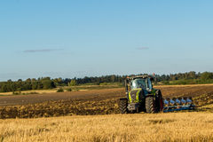 Agriculture plowing tractor on wheat cereal fields Royalty Free Stock Image