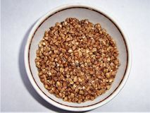 Brown grits buckwheat in a cup a tasty, useful, fragrant product, porridge royalty free stock photography