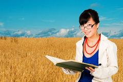 Agriculture specialist. Asian woman with a book in wheat field - agriculture specialist Stock Photography