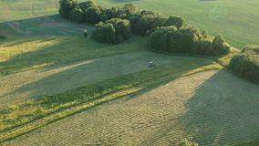 Agriculture tractor cut harvesting summer hay, aerial view stock footage