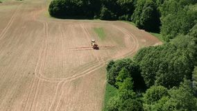 Agriculture tractor in early spring spraying farmland field with crop sprouts, aerial stock footage