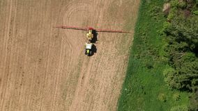 Agriculture tractor in early spring spraying field with crop sprouts, aerial stock video footage