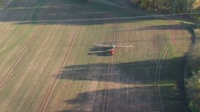 Agriculture tractor in evening spraying autumn time crop field with sprouts, aerial stock video