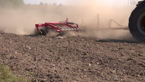 Agriculture tractor on farm field with cultivator stock footage