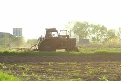 Agriculture. Tractor plowing field in sunset. Cultivated field. Agronomy, farming, husbandry. Concept stock photography