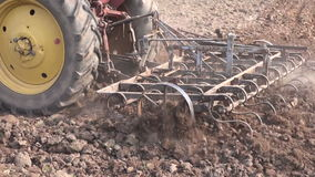 Agriculture tractor plowing spring farm field with metal  harrow stock video footage
