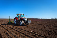 Agriculture tractor sowing seeds and cultivating field. Royalty Free Stock Photos