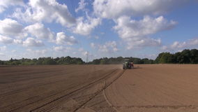 Agriculture tractor sowing wheat seeds in field stock video