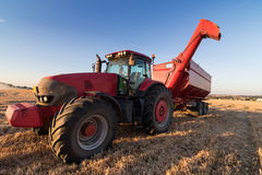 Agriculture tractor on a stubble field Stock Images