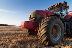 Agriculture tractor on a  stubble field. Agriculture tractor and tow trailer waiting to be filled at grain campaign at sunset on a stubble field Royalty Free Stock Photos
