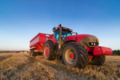 Agriculture tractor and trailer on a stubble field Stock Photography