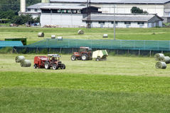 Agriculture works. Agriculture motive - Agriculture motive - two tractors in a field making hay balls Royalty Free Stock Photography