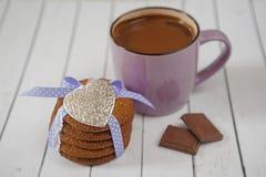 Agrida com cacau quente as cookies cobertas do pão-de-espécie, a lembrança metálica do coração e os pedaços de chocolate em um ta Imagem de Stock