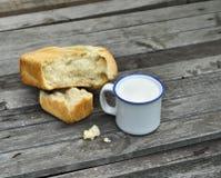 Agrida com leite e naco de pão na tabela velha Foto de Stock Royalty Free
