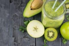 Agrida com um cocktail recentemente preparado do abacate do batido com duas palhas em uma tabela de madeira Alimento do vegetaria Imagem de Stock
