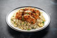 Agridoce picante da galinha alaranjada com arroz dos ovos fritos em uma placa foto de stock