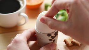 Agrietando y comiendo el huevo hervido para el desayuno