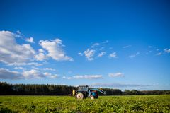 Agrikultura tractor cultivates the soil on the field.  Royalty Free Stock Photography