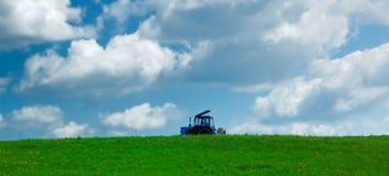 Agrimotor en campo del verde del cielo foto de archivo