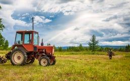 Agrimotor en el campo con el heno Foto de archivo libre de regalías