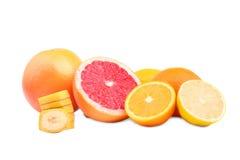 Agrios enteros y cortados por la mitad, aislados en un fondo blanco Plátano dulce y tajado, pomelos maduros, naranjas y un limón Foto de archivo