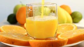 Agrios frescos Imágenes de vídeo del concepto de una dieta sana y de dieta El zumo de naranja se vierte en un vidrio, con un back almacen de video