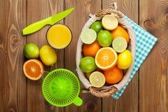 Agrios y vidrio de jugo Naranjas, cales y limones Foto de archivo libre de regalías
