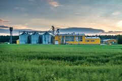 Agro-processing plant for processing and silos for drying cleaning and storage of agricultural products, flour, cereals and grain. With beautiful clouds stock image