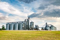 Agro-processing plant for processing and silos for drying cleaning and storage of agricultural products, flour, cereals and grain. With beautiful clouds stock photography