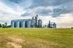 Agro-processing plant for processing and silos for drying cleaning and storage of agricultural products, flour, cereals and grain. With beautiful clouds royalty free stock image