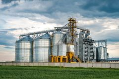 Agro-processing plant for processing and silos for drying cleaning and storage of agricultural products, flour, cereals and grain. With beautiful clouds stock images