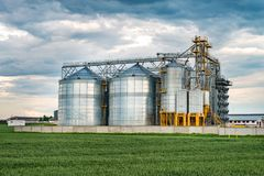 Agro-processing plant for processing and silos for drying cleaning and storage of agricultural products, flour, cereals and grain. With beautiful clouds stock photo