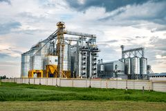 Agro-processing plant for processing and silos for drying cleaning and storage of agricultural products, flour, cereals and grain. With beautiful clouds royalty free stock photo