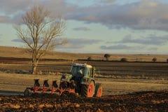 Agro trattore che ara la terra Fotografia Stock