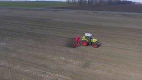 Agrobusiness - veldwerk in de vroege lente De tractor cultiveert het land op het gebied, luchtvideo stock video